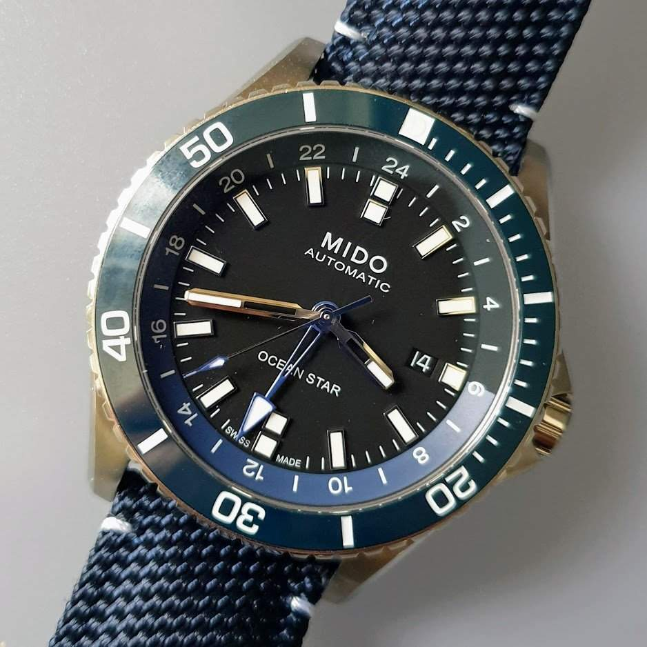 Mido Ocean Star GMT and its black dial on a blue strap